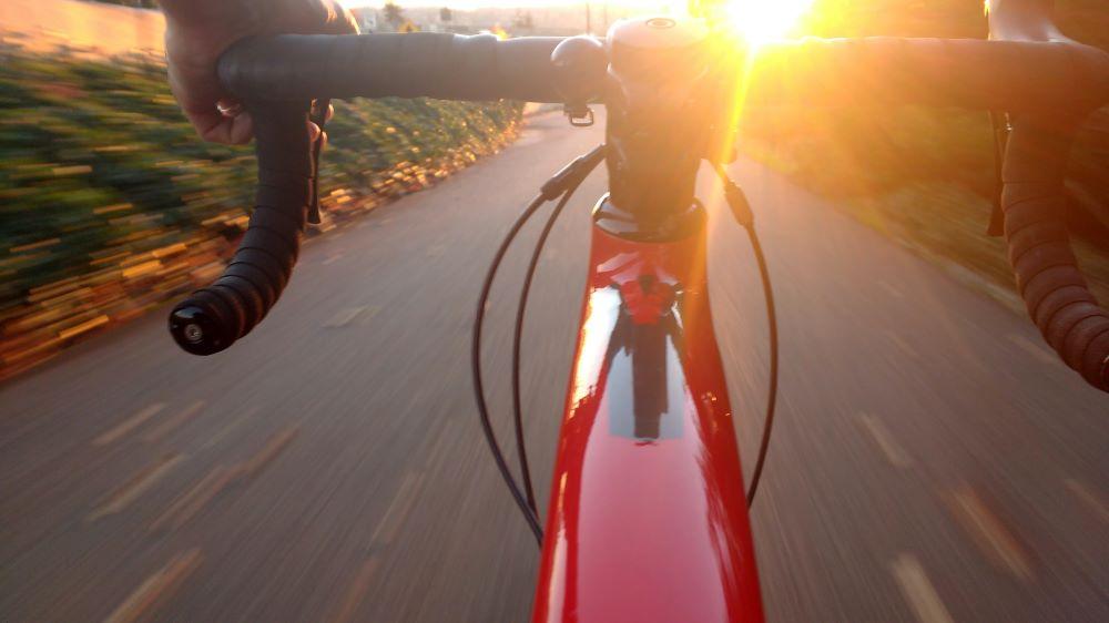 A bike being ridden at sunset