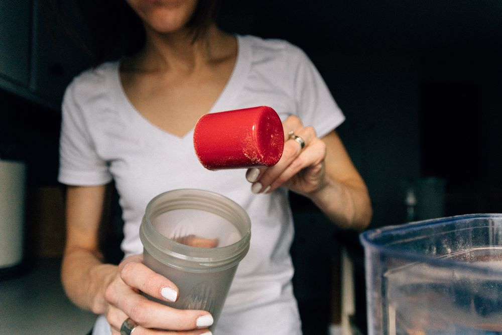 Women fills shaker with protein