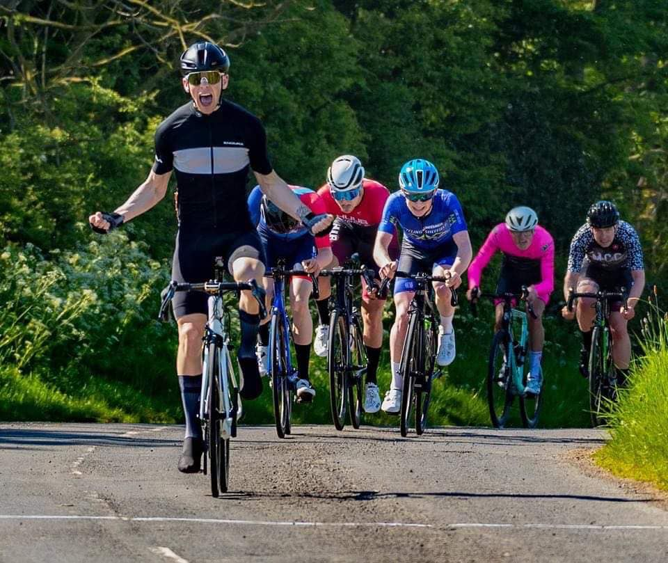 Alexander Macrae raises his arms in victory as he wins a cycling race