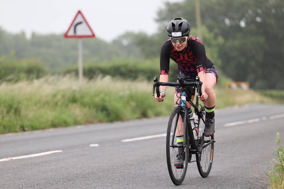 A Blackzone Coaching athlete cycling on a road